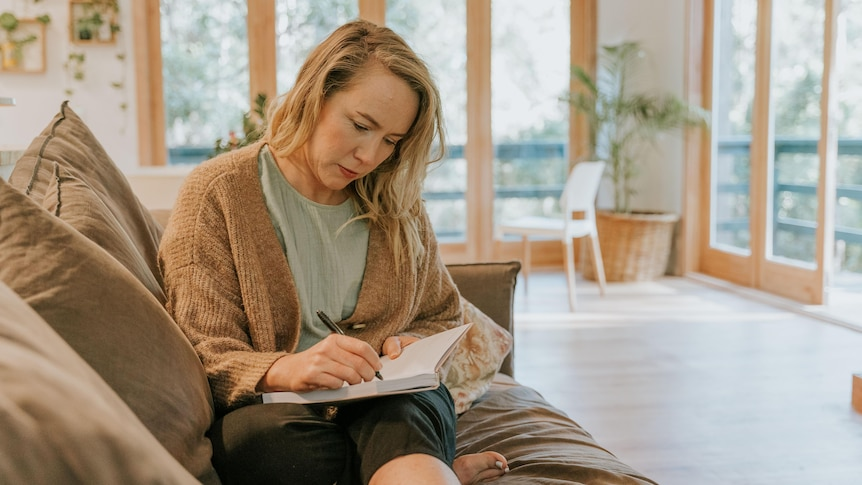 A woman sits on a couch, writing in a journal.