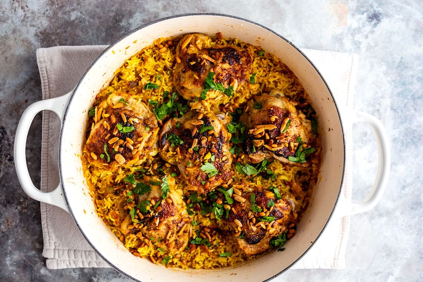 Saffron chicken and rice bakes in one pan and is served with toasted nuts and parsley, an easy dinner.