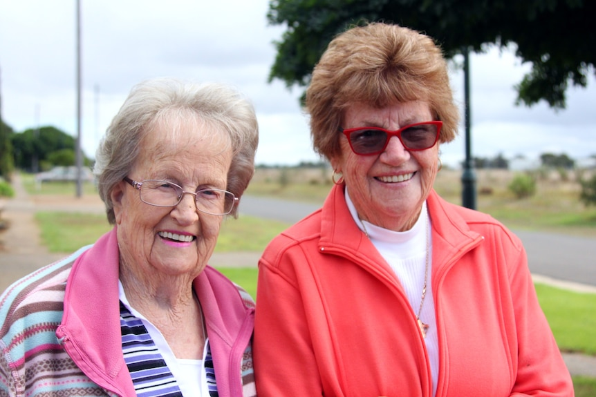 Two women in their 80s standing on a suburban street with a footpath on one side and paddocks on the other