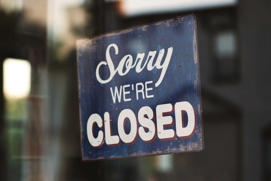 Sorry we're closed sign hanging on glass door, a reminder to close old unused bank accounts once establishing new ones.
