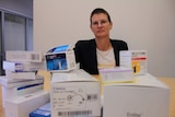 A woman sits behind a large pile of pharmaceutical boxes