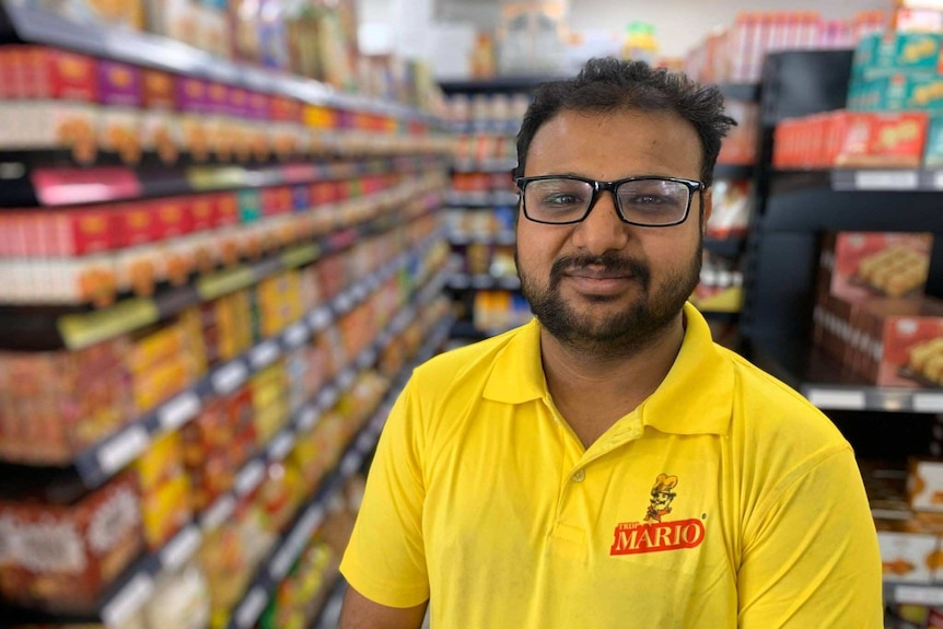 An Indian man in glasses stands in a shop aisle