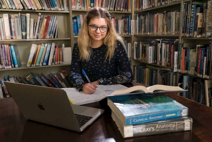 Jasmyn Lloyd studies at a desk, surrounded by books.