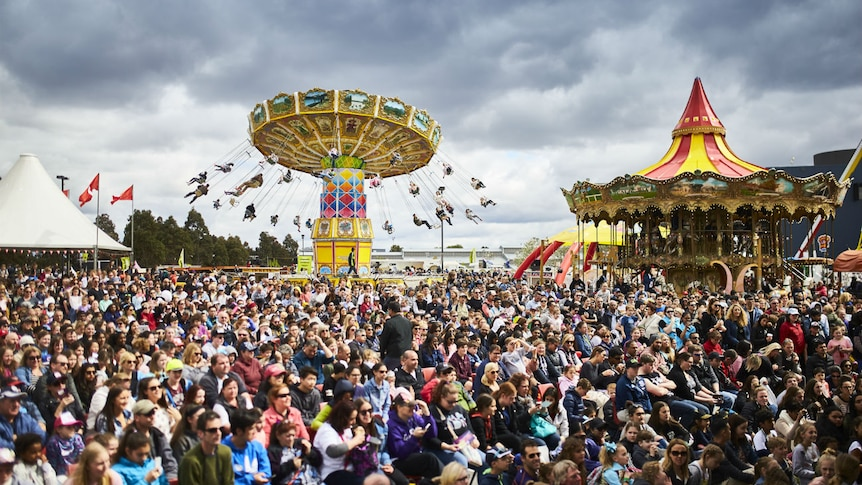 Play Audio. A large crowd gathers under a grey sky. There are rides and marquees in the background.. Duration: 9 minutes 4 seconds