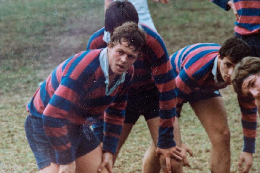 A teenager in a red and blue striped jersey plays rugby union.