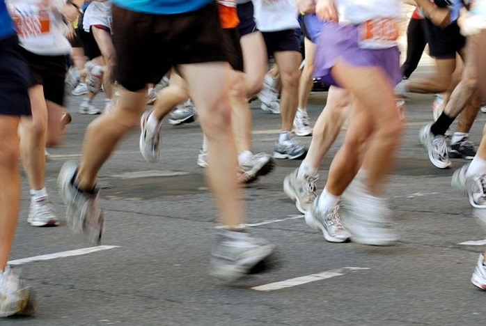 Lower half of body of group runners on a road with legs slightly blurred