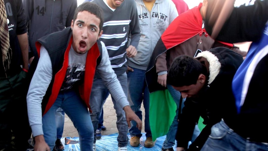 Libyan protesters stomp on a poster of leader Moamar Gaddafi