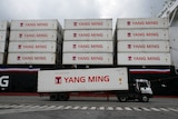 A truck carrying a white shipping container moves past a ship loaded with identical containers stacked four high.