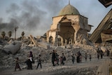 Women and children walk with rubble and a crumbling edifice in the background.