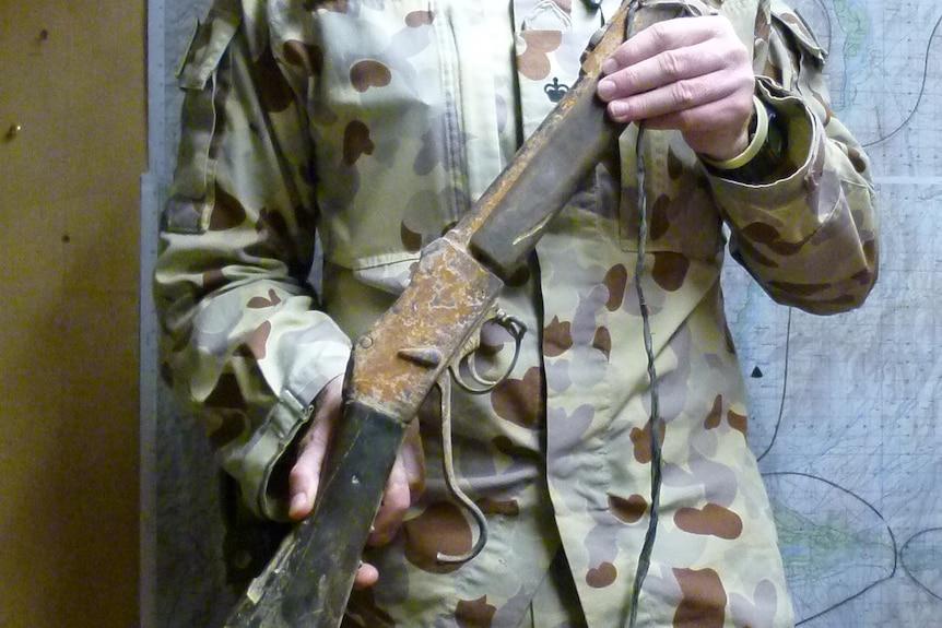 Lieutenant Colonel Darren Huxley in uniform holding the Martini-Henry 1880 rifle