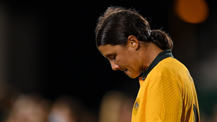 Sam Kerr has her head bowed and lips pursed