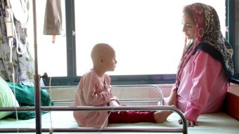 A child attached to a drip sits on a hospital bed with her mother.