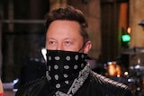 Miley Cyrus, Elon Musk and Cecily Strong on a tv studio stage wearing masks