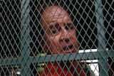 James Ricketson sits behind a cage in a prison truck