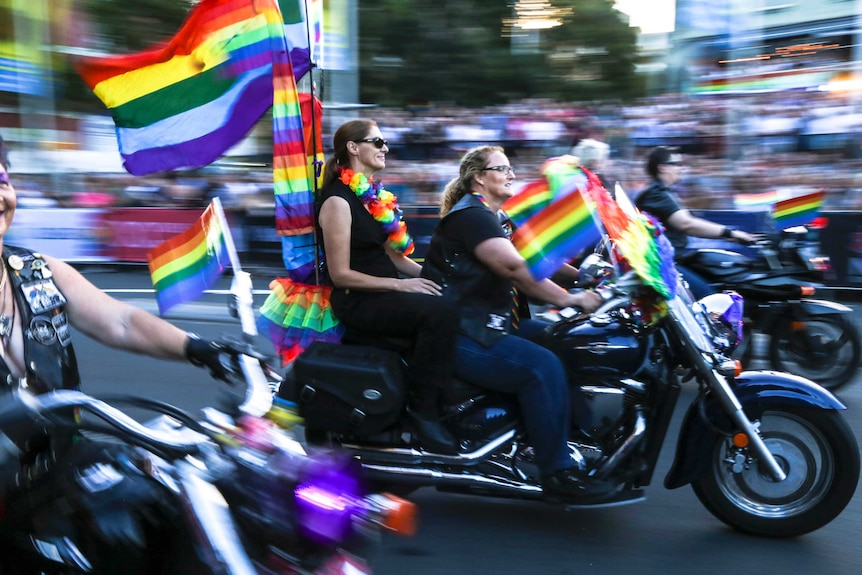 Two women ride a black motorbike along a parade route filled with crowds, there are lots of rainbow flags attached to the bike.