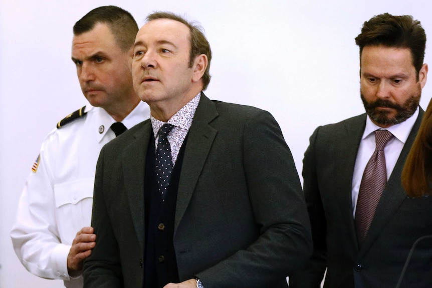 Actor Kevin Spacey enters the courtroom accompanied by a uniformed guard.