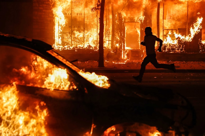 The outline of a man is seen as he runs between a burning building and a car set ablaze.