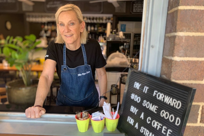 A woman in a black t-shirt and denim apron stands behind a cafe counter.