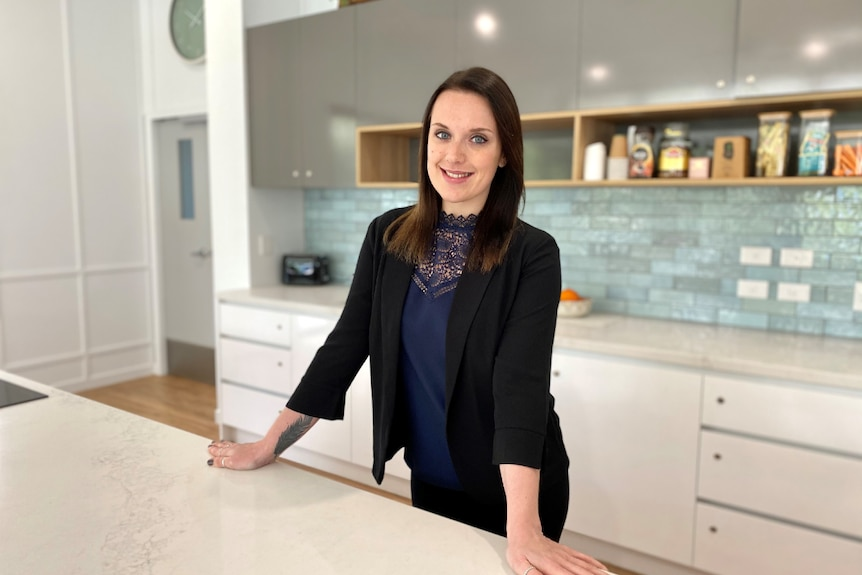 Woman in corporate attire stands in a large kitchen with white marble bench.