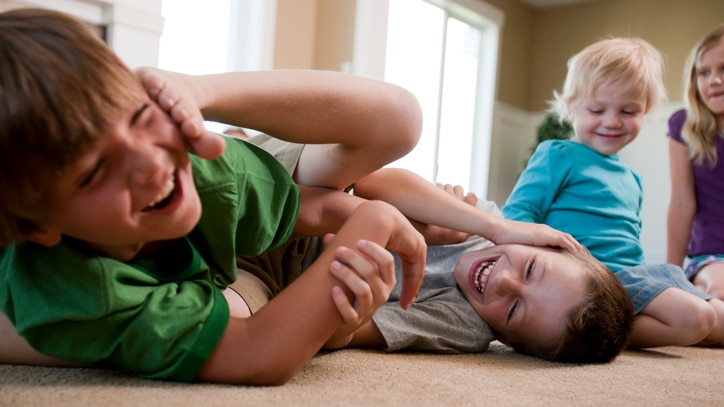 Two young boys play fighting with other young children looking on