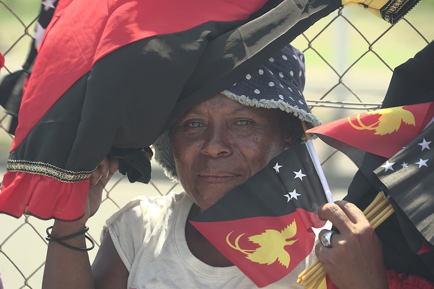 A street vendor holds PNG-themed flags and a meri blouse to her face at a market.