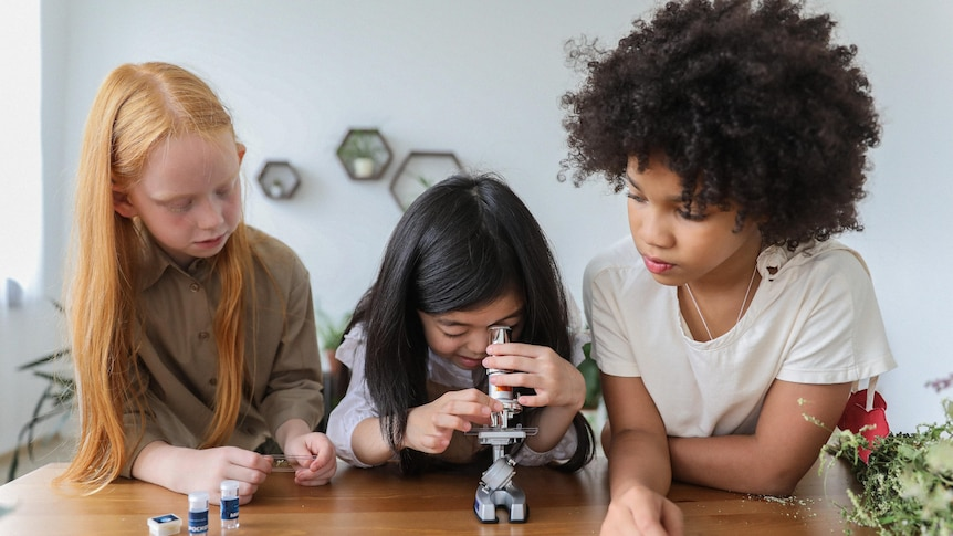 A child looks into a microscope, while two other children watch