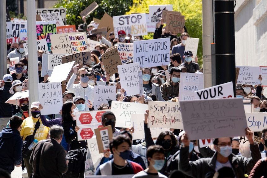 A large crowd of protesters wear masks and carry signs as they walk on sunny street.
