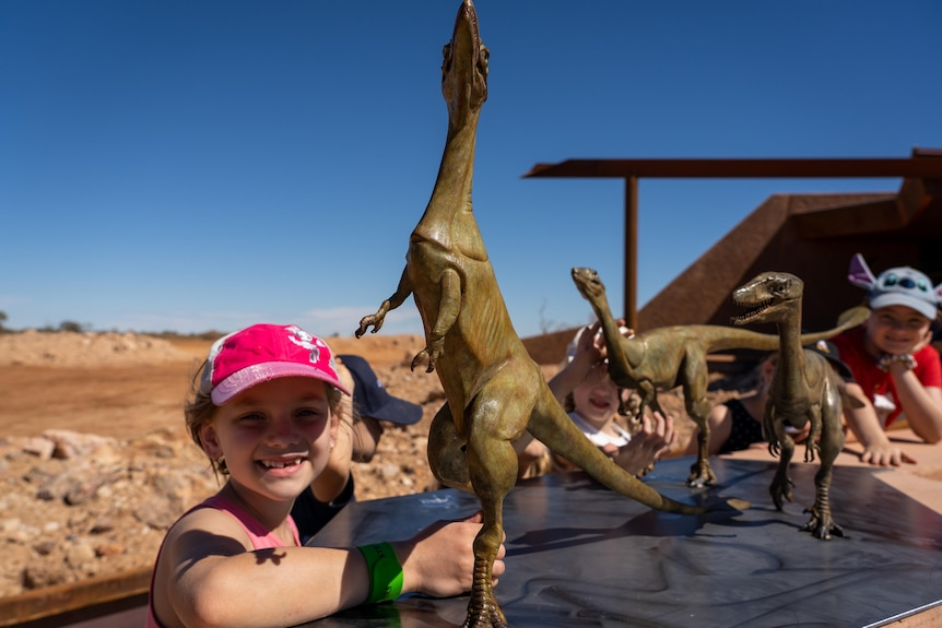 A group of kids pose for photos with tiny dinosaur statues.
