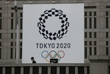A man walks past a large banner promoting the Tokyo 2020 Olympics.
