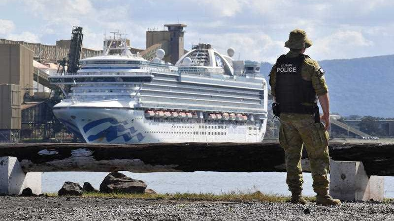 A man in army uniform on a shoreline looking at a cruise ship.