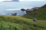 A man sits on a grassy hill, looking out at the ocean.