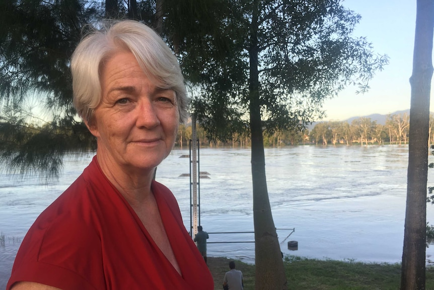 A woman with white hair and a red top stands near a river