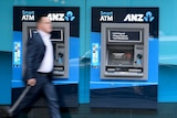 A man in a suit walks passed an unused ATM