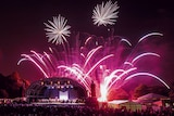 Fireworks light up the sky above a stage filled with a symphony orchestra