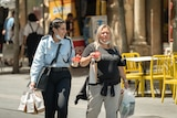Two women holding shopping bags and with masks under their chins laugh on an Israel street.