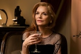A scene from the film French Exit with Michelle Pfeiffer in fancy dress holding a glass of wine