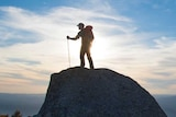 A hiker stands on a big granite rock with the sun and blue sky and white clouds behind him on Mt Buffalo.