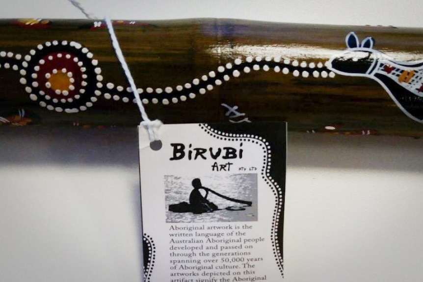 A description tag on a didgeridoo made by Birubi Art.