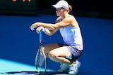 Ash Barty crouches and leans on her racquet during a break in her Australian Open match against Karolína Muchová.