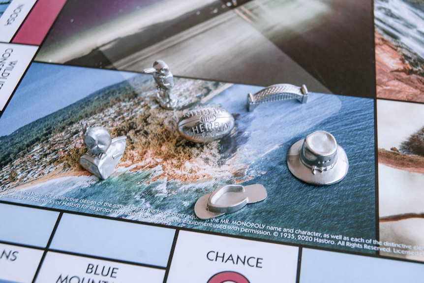 Close up of Monopoly board featuring Australian locations, with silver playing tokens including the Harbour Bridge and Kangaroo