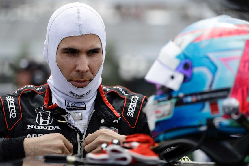 A man wearing an open-faced balaclava zips up his race suit with his helmet in the foreground