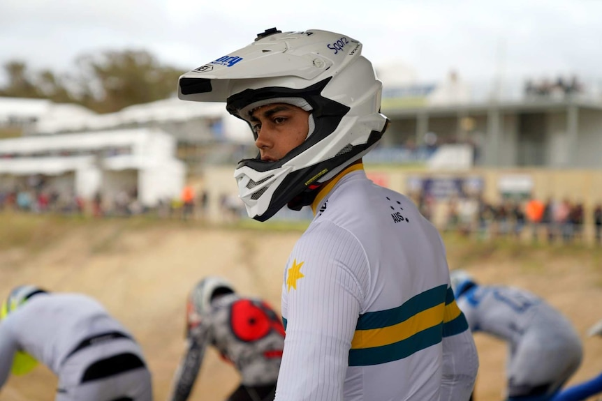 A young man in Australian sports colours and helmet.