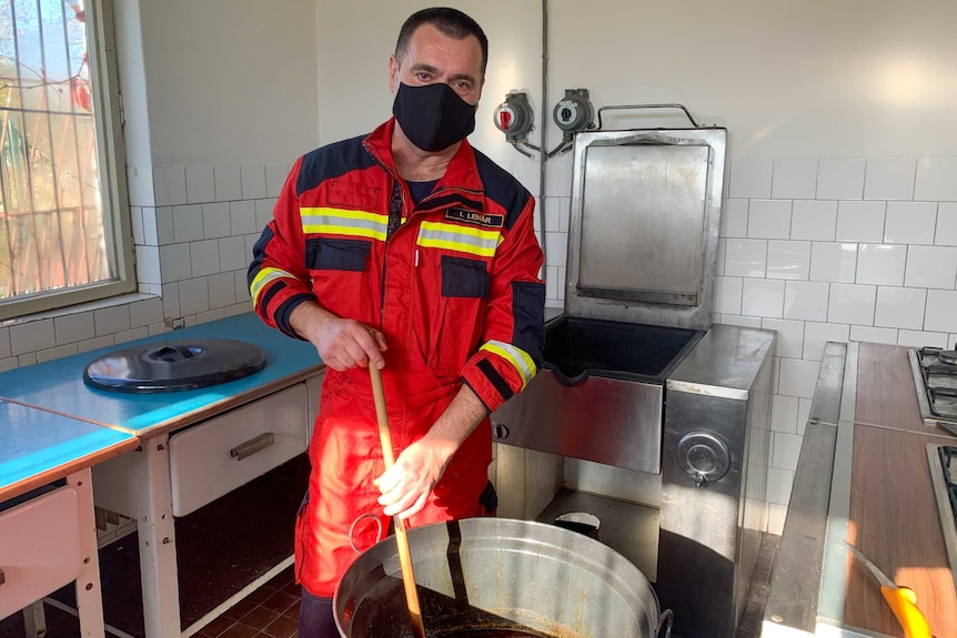 A man in a face mask holding a ladle in a giant pot of goulash.