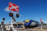 A train travels over a road with boom gates and flashing lights to warn drivers.