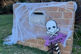"""A mailbox with cobweb decorations and a """"Happy Halloween"""" sign."""