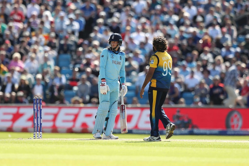 A batsman stares after being caught behind, while the bowler eyes him waiting to celebrate.