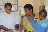 A church health worker gives medicine to a woman and a baby at a clinic.