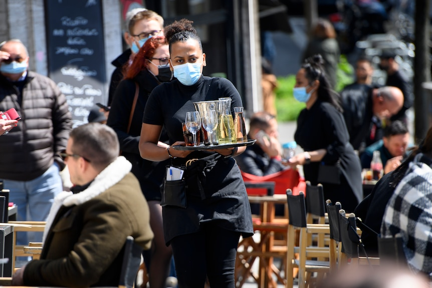 A waitress wears a mask as she carries a tray of alcoholic drinks in an outdoor restaurant as patrons sit on chairs