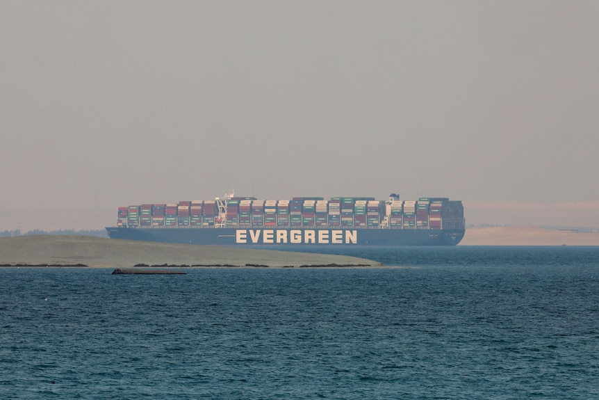 A loaded container ship is seen sitting in a lake between flat expanses of parched land.
