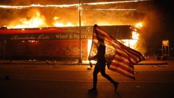 A protester carries an upside down US flag as they walk past a burning building on an empty street.